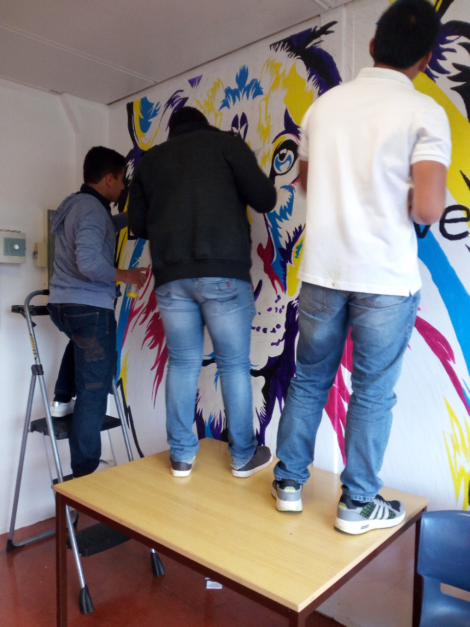 Three students painting a vibrant mural on the wall.