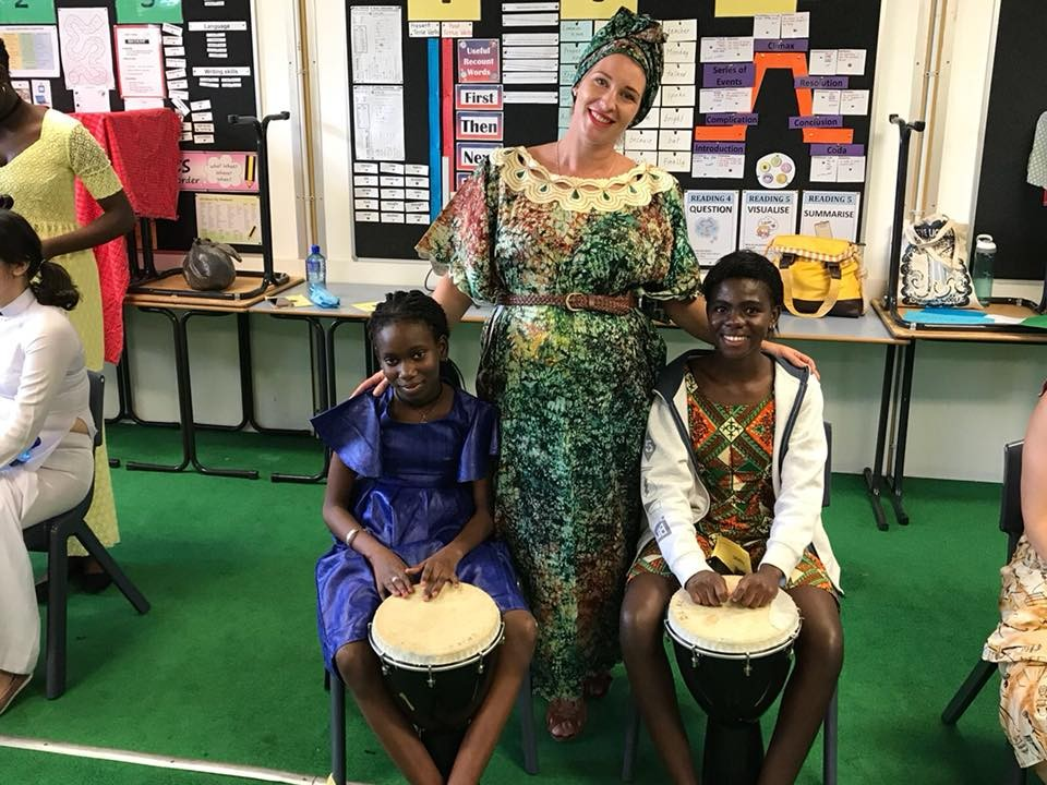 Teacher Ella Linton with students from Africa demonstrating their drums.
