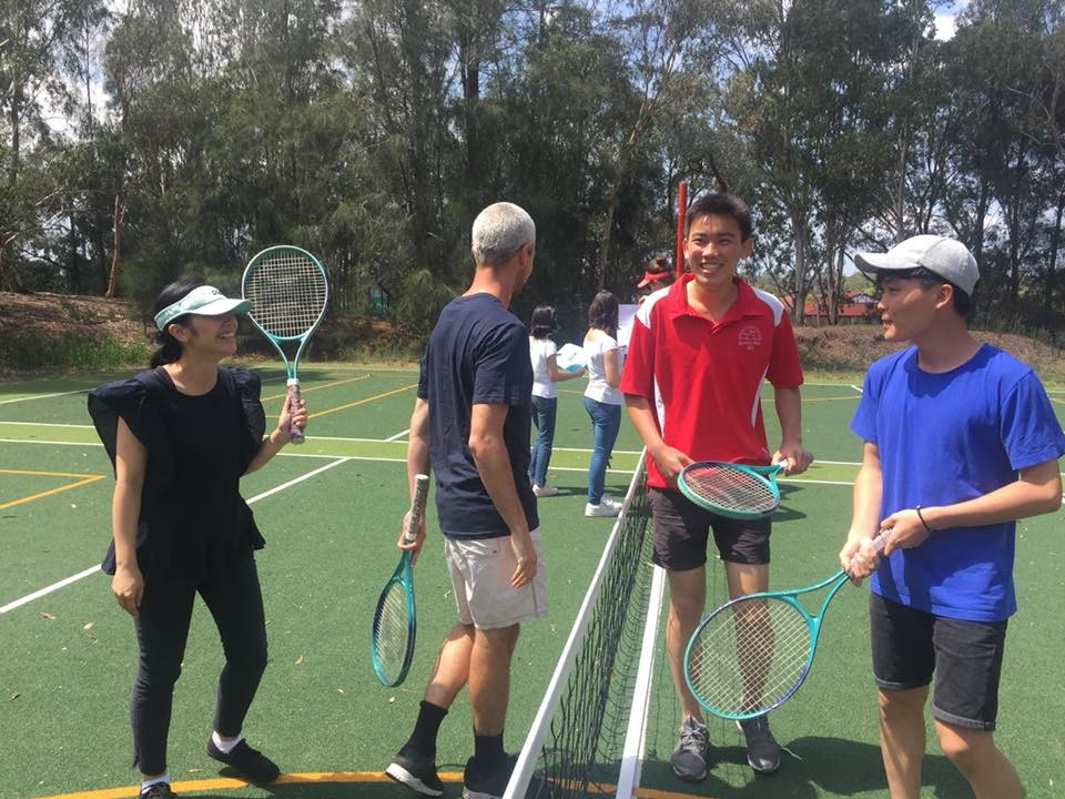 Teachers and students tennis enjoying a friendly tennis game.