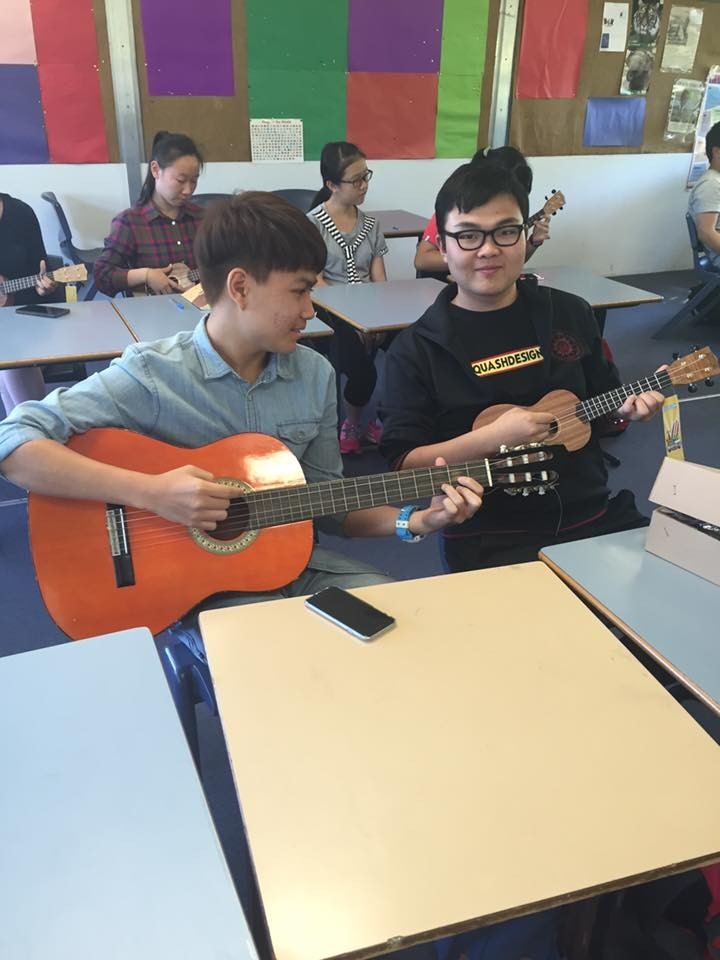 A boy playing a guitar while another boy plays the ukelele.